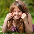 Girl Lying On Grass While Playing With Hair In Park — Stock Photo