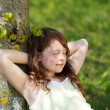 Girl With Eyes Closed Leaning On Tree Trunk In Park — Stock Photo #26217939