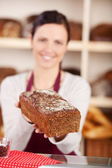 Bakery assistant selling bread — Stock Photo
