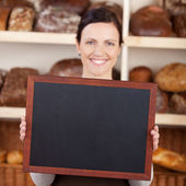 Bakery worker holding a blank chalkboard — Stock Photo