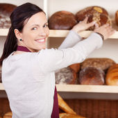 Friendly female bakery employee — Stock Photo