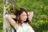 Girl With Eyes Closed Leaning On Tree Trunk In Park — Stock Photo