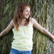 Girl Looking Away While Leaning On Tree Trunk — Stock Photo