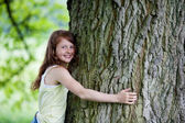 Cute little girl hugging tall tree — Stock Photo