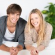 Smiling young couple leaning on sofa — Stockfoto