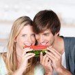 Couple eating melon together — Stockfoto