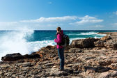 Woman with rucksack watching the ocean — Stock Photo
