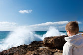 Boy Looking At Waves Splashing On Rock At Beach — Stock Photo