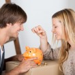 Stock Photo: Couple saving money