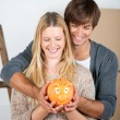 Couple between transport boxes holding piggybank — Stock Photo