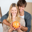 Stock Photo: Couple between transport boxes holding piggybank