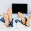 Couple lying barefeet on sofa — Stock Photo #26248585