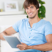 Young man sitting on sofa working with tablet — Stock Photo