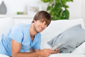 Man lying on sofa reading tablet — Stock Photo
