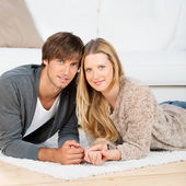 Portrait of a couple lying on the floor — Stock Photo