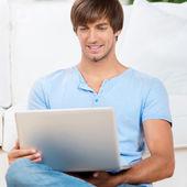 Glücklicher mann sitzt auf dem sofa mit notebook — Stockfoto