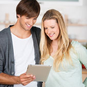 Smiling couple looking at tablet — Stockfoto
