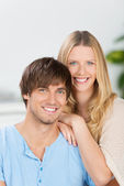Happy couple sitting at home embracing — Stock Photo