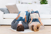 Relaxed couple lying on the floor reading — Stock Photo