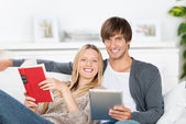 Laughing couple reading book and ebook — Stock Photo