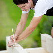 Carpenter making markings on a roof beam — Stock Photo #26254487