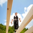 Carpenter standing on the roof beams — Stock Photo #26254599