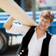 Carpenter carrying a large wood plank — Stock Photo #26254831