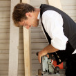 Carpenter with a saw — Stock Photo