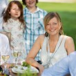 Young Woman With Family Sitting In Lawn — Stock Photo