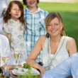 Stock Photo: Young Woman With Family Sitting In Lawn