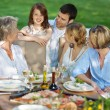 Happy grandmother with family sitting outdoors — Stock Photo