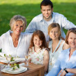 Multi Generation Family Smiling Together At Dining Table — Stock Photo