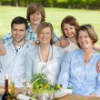 Family Smiling Together At Dining Table — Stock Photo #26259429