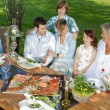 Happy family sitting together in the garden — Stockfoto