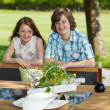 Brother And Sister Leaning On Bench At Lawn — Stock Photo #26259669