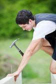 молодые карпентер, вбить гвоздь на балке — Стоковое фото