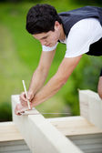 Carpenter making markings on a roof beam — Stock Photo