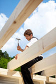 Carpenter working on the top of the roof structure — Stock Photo