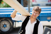 Carpenter carrying a large wood plank — Stock Photo