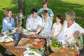 Happy family sitting together in the garden — Stock Photo