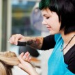 Young woman working at the hairdresser — Stockfoto