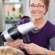 Hairdresser Holding Comb And Blow Dryer In Salon — Stock Photo