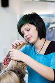 Junge friseurin mit tattoo am arbeitsplatz — Stockfoto