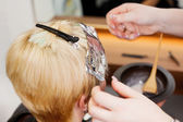 Blonde female having new highlights at hair salon — Stock Photo
