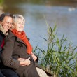 Happy senior couple enjoying the sun near a lake — Stock Photo