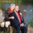 Happy senior couple enjoying near a lake — Stock Photo