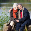 A senior couple posing by the lake — Stock Photo