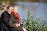 Happy senior couple enjoying the sun near a lake — Stock Photo