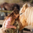 Young girl demonstrating affection for her horse — Stock Photo #26297651