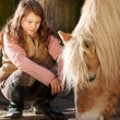 Girl observing a horse feeding — Stock Photo